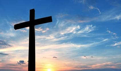 Cross over bright sunset background